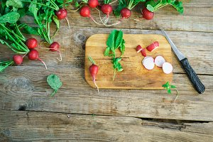 bundle of bright fresh organic radishes with leaves on rustic table