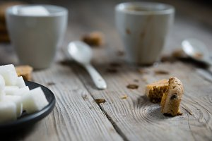 Two cups of coffee and refined sugar and cookie crumbs.