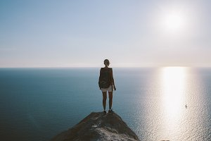 woman hiker stands on cliff