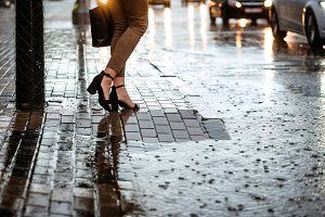 Woman crosses wet street with large pool. Closeup legs. Heavy rain.