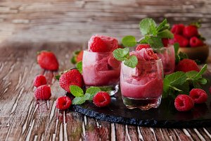 frozen yogurt, sorbet with strawberries, raspberries and mint, selective focus
