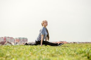happy young girl doing stretching exercises in summer park