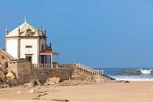 White stone chapel on a sandy beach
