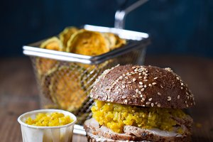 Burger with sliced roast meat and cucumber relish, zucchini chips