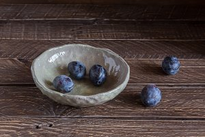 plums in a clay bowl