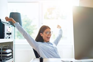 Joyous woman in small office with extended arms