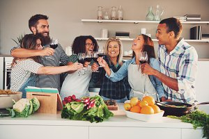 Fun group toasting wine glasses while cooking