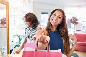 Vivacious young woman shopper grinning at camera