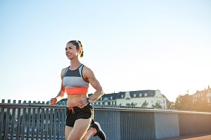 Confident woman jogging along bridge