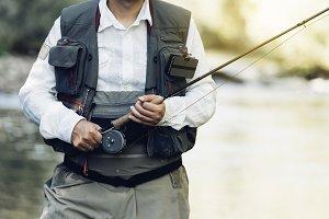 Fisherman using flyfishing rod.