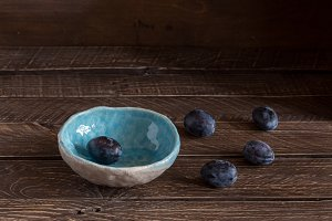 blue  ceramic bowl with plums