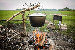 cooking fish soup in pot on bonfire.