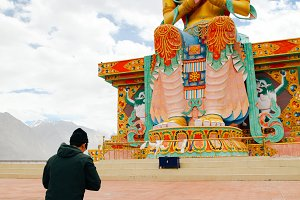 Man praying in Tibetan Buddhist temple of Maitreya in Ladakh, India - Religion and Worship concept