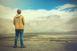 Young male traveler standing on the sand cliff, thinking about or looking forward to something in Leh, Ladakh,India
