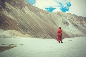Woman in traditional Indian dress standing in desert in Ladakh, India (Vintage tone)