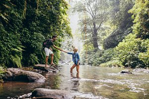 Young couple walking across stream