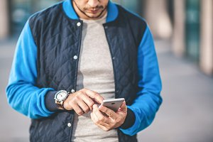 Man in blue jacket using smartphone