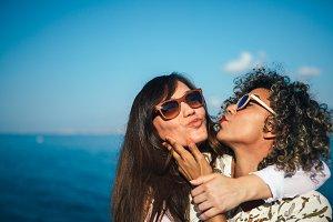 Two girl friends kisses joyfully