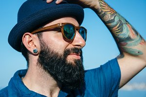 Bearded man in sunglasses with hat