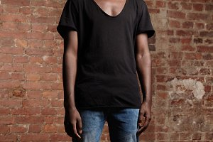 Cropped portrait of fashionable young African student dressed in trendy t-shirt and jeans, relaxing indoors. Attractive black man with fit athletic body standing isolated in studio with red brick wall