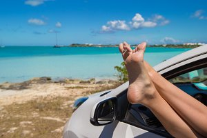 Close up female feet from the window of a car on background tropical beach