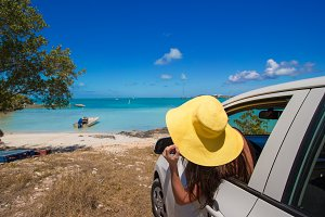 Woman in a car on background beach