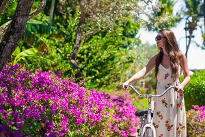 Young beautiful woman riding a bike at flowering garden