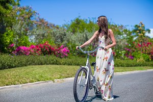 Young girl riding a bike on tropical resort