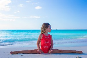 Little girl sitting on the splits at white sandy beach
