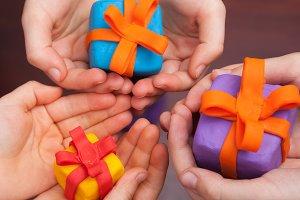 Children holding plasticine presents