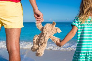 Young father with little daughter holding bunny toy on caribbean beach
