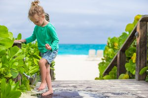 Little cute girl washes out the sand from her feet on tropical beach