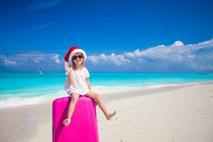 Little girl in Santa hat sitting on a large suitcase at tropical beach