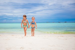 Adorable little girls having fun during beach vacation