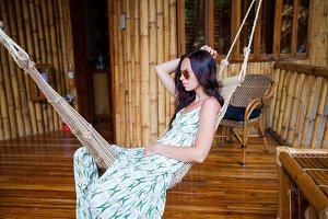 Beautiful brunette woman in long dress relaxing in hammock