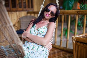 Beautiful brunette woman relaxing in hammock at exotic hotel on Philippines