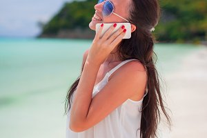 Young beautiful woman at beach talking by her phone