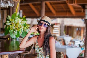 Beautiful brunette woman in long dress and hat relaxing in beach restaraunt