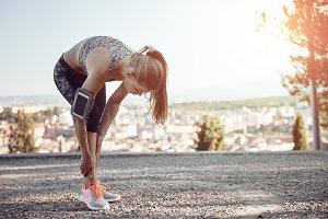 Woman athlete massaging painful leg