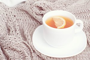 cup of tea on gray blanket in bed.