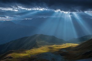 Mountain valley in beams of sun