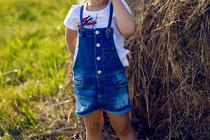 little girl in the haystack in a hat