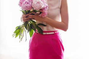 girl in pink skirt and white jacket in the hands holding a bouquet with peonies