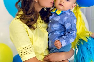 happy mom in a yellow dress holds young son in blue clothes