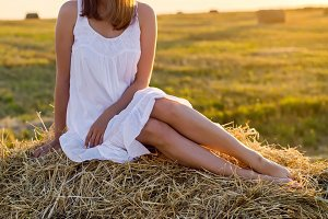 young girl in a white dress is sitting on the haystack