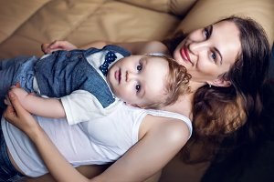 happy mother in white tank top laying with my son on a light sofa