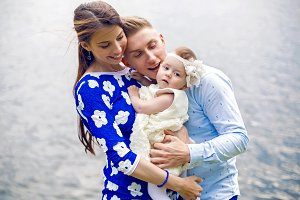 happy young couple with baby girl standing in water