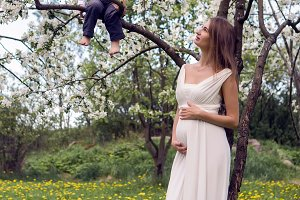 pregnant girl with long hair wearing a white dress standing  his son on the tree