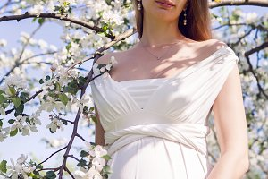 pregnant girl with long hair wearing a white dress standing