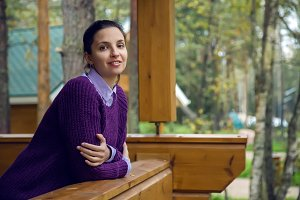 young girl in a purple sweater and black jeans